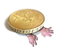 Heavy burden of debt and money worries. Composition photo of a pair of hands struggling to climb out from under a large pound coin, depicting someone trying to Royalty Free Stock Image