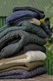 Heavy cable knit fishermen's sweaters. Stack of chunky Irish wool cable knit and Aran winter sweaters plus socks in fall and winter colours in a pretty Irish Royalty Free Stock Image