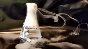 Heavy carbon dioxide smoke coming out of conical flask  in slow motion. Heavy carbon dioxide smoke coming out of conical flask and touching the black surface in stock video footage