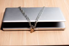Heavy chain with a padlock around a laptop on table.  stock images