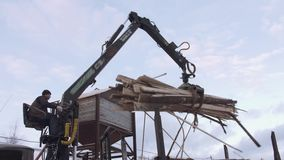 Heavy claw loader unloads timber scraps from heavy truck at sawmill facility. Cold cloudy winter day stock video