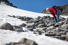 Heavy climbing on stony and snowy mountain slope to the pass, mature man Stock Image