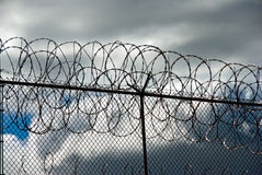 Heavy cloud over barb wires Stock Photography