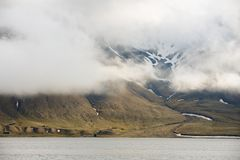 Heavy clouds over the arctic shore of the polar archipelago of Spitsbergen near Longyearbyen, Norway. stock photo