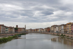 Heavy clouds over Arno River and waterfront buildings, Pisa Stock Photos