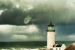 North Head Lighthouse under stormy skies. Heavy clouds from stormy skies hang over the ocean while the ever present North Head Lighthouse stands in the Royalty Free Stock Photography