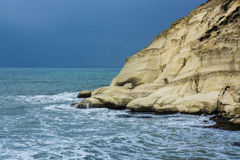 Heavy clouds with stormy waves beating against rocks and cliffs Stock Photo