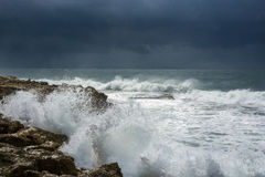 Heavy clouds with stormy waves beating against rocks and cliffs Royalty Free Stock Image
