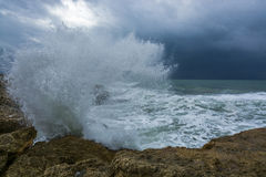Heavy clouds with stormy waves beating against rocks and cliffs Stock Photos