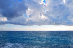 Heavy clouds and vast deep blue sea royalty free stock image