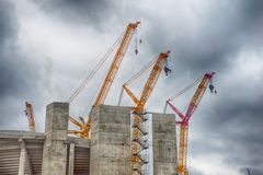 Heavy construction cranes erecting concrete building Royalty Free Stock Image