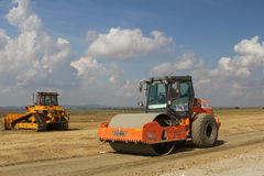 Heavy construction equipment compacting soil on a runway construction site. TULCEA, ROMANIA - SEPTEMBER 26: Heavy construction equipment compacting soil on a Royalty Free Stock Photo