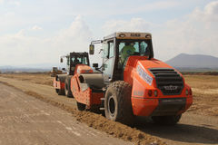 Heavy construction equipment compacting soil on a runway construction site Stock Image