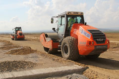 Heavy construction equipment compacting soil on a runway construction site. TULCEA, ROMANIA - SEPTEMBER 26: Heavy construction equipment compacting soil on a Stock Image