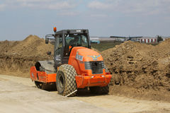 Heavy construction equipment compacting soil on a runway construction site Stock Photo