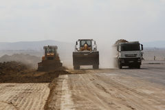 Heavy construction equipment working on a runway construction site Royalty Free Stock Photo