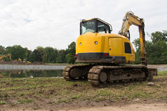 Heavy construction equipment. Yellow excavator on the construction site Stock Image