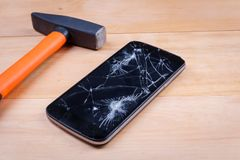 A hammer is next to a smartphone with a broken screen. On a wooden background. Close-up. A heavy construction hammer is next to a modern black smartphone with a royalty free stock image