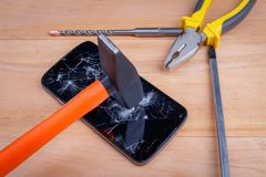 A hammer breaks a modern black smartphone, next to it are various tools. On a wooden background. Stock Photography