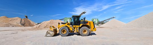 Heavy construction machine in open-cast mining - wheel loader tr. Ansports gravel in a gravel plant stock images