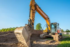 Heavy construction machinery performs work on a construction site. A heavy construction machinery performs work on a construction site royalty free stock image