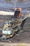 Heavy construction tipper trucks dump coal to the conveyor Stock Photos