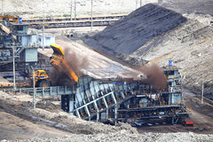 Heavy construction tipper trucks dump coal to the conveyor Stock Photos