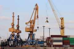 Heavy cranes and containers at the port Stock Image