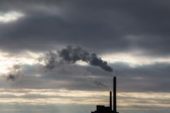 Heavy dark cloud of smoke from industrial chimney in sunset with copy space stock images