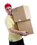 Heavy delivery. Young delivery man delivering two heavy parcels Stock Images
