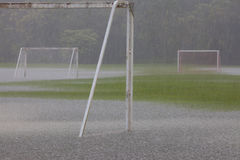 Heavy downpour on empty, grass soccer field with pooling water. Torrential, heavy rain resulting in standing water on a green grass soccer field in tropical Royalty Free Stock Photo