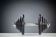 Heavy Dumbbell. Front image of a heavy fitness dumbbell lying on a white surface stock images