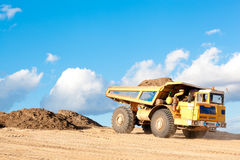 Heavy dump truck at a construction site. Heavy dump truck unloads soil on the sand at a construction site royalty free stock photo
