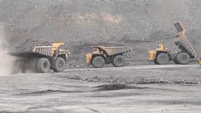 Heavy dump truck rides along other dump trucks. In open pit stock footage