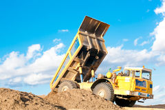 Heavy dump truck unloading soil. Heavy dump truck unloads soil on the sand at a construction site royalty free stock images