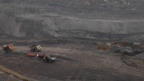 Heavy dump trucks ride along the open pit. Heavy dump trucks ride along the coal open pit stock video
