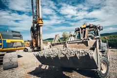 Heavy Duty Bulldozer Moving Gravel On Highway Construction Site. Multiple Industrial Machinery On Construction Site