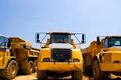 Heavy duty construction trucks. A view of the front of yellow, heavy duty earthmoving trucks on a construction site Stock Images