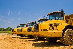 Heavy duty construction trucks. A view of the front of a line of heavy duty earthmoving trucks on a construction site Stock Photos