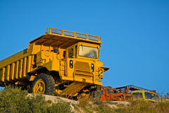 Heavy duty dump trucks. Old heavy duty dump truck and other abandoned trucks at the background royalty free stock image