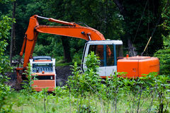 Heavy Duty Equipment Weed Control. A telephoto shot of a backhoe and a small front end loader siting idle in a clearing in an overgrown field at the edge of a Royalty Free Stock Photography
