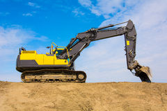 Heavy duty excavator on the skyline. Heavy duty excavator, digger or backhoe on top of an earth embankment on the skyline against a sunny blue sky, side view Royalty Free Stock Images