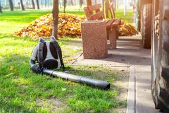 Heavy duty foliage blower lying on clean grass in city park in autumn. Seasonal leaves cleaning and removal service in. Fall stock photos