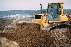 heavy duty machinery, details of excavator pushing earth and building highway. construction site Royalty Free Stock Images