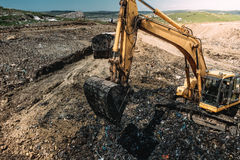 Heavy duty machinery, excavator digging hole and loading garbage into dumper trucks. Industrial heavy duty machinery, excavator digging hole and loading garbage Stock Images