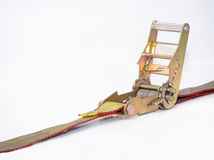 Heavy duty ratchet strap. A bronze gold coloured heavy duty ratchet strap as used in securing items in or on trailers and trucks stock photo