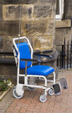 HEAVY DUTY WHEELCHAIR, HOSPITAL CHAIR. Heavy duty wheelchair outside a building with close up of hospital chair Royalty Free Stock Images