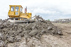 Heavy earthmover construction machine is moving earth at buildin. View on heavy bulldozer while he moving, leveling ground at construction site Royalty Free Stock Image