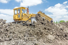 Heavy earthmover is moving earth at building site. Dump truck is. View on heavy bulldozer while he moving, leveling ground at construction site.  Heavy wheels Stock Image