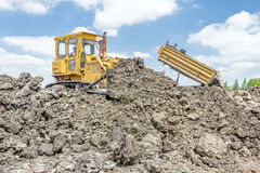 Heavy earthmover is moving earth at building site. Dump truck is. View on heavy bulldozer while he moving, leveling ground at construction site.  Heavy wheels Royalty Free Stock Photo